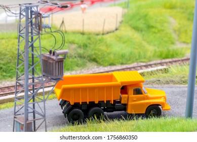Orange truck in H0 scale on model train road