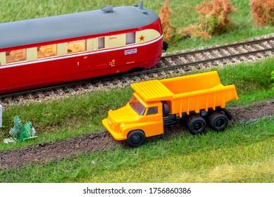 Orange truck on model train layout next to historic passenger train