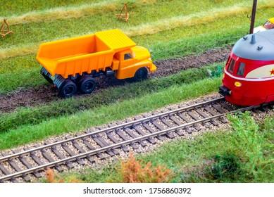 Orange truck on model train layout pass by passenger train