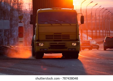 Orange truck on a road at sunset