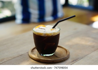Orange Twist Cold-Brew Iced Coffee - A glass of Americano mixed with orange juice on wooden table background.