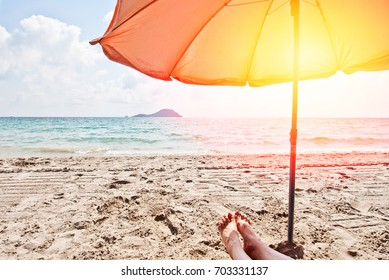 Orange umbrella on the beach, beautiful sea view, vacation relaxing pleasure trip, sunbathing, first-person view