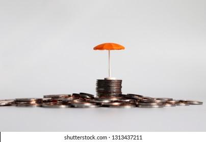 An orange umbrella on a pile of coins.