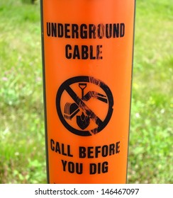 Orange underground cable warning sign.  Call before you dig.
