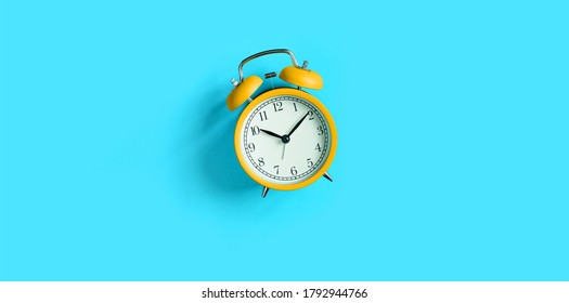 Orange vintage alarm clock on Turquoise blue background. Top view, flat lay, copy space