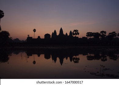 orange and violet sunrise over famous angkor wat temple with lake and reflection in the water with lillypad