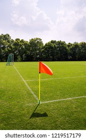 Orange vivid corner flag on fresh green football ground, trees in background, sunny summer day