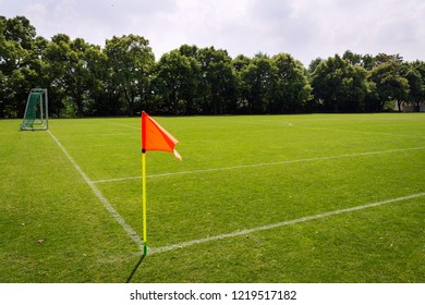 Orange vivid corner flag on fresh green football ground, trees in background, sunny summer day