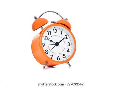 Orange Wake Up Call A classic ringing alarm clock behind a white background