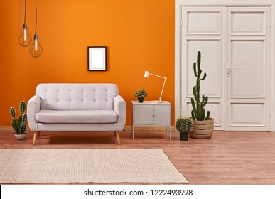 Orange wall and grey sofa with white classic door background. Modern orange lamp with vase of plant interior room.