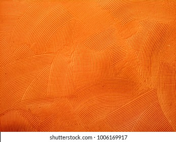 Orange wall with rustic texture made with mortar.