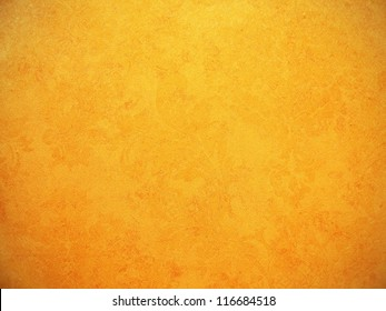 Orange wallpaper with rough surface texture.