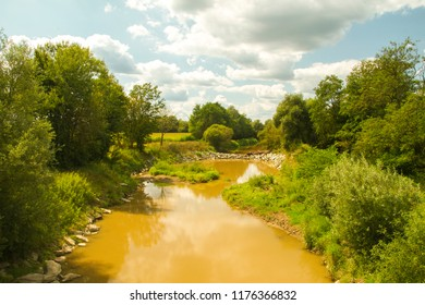 Orange water of the Raab, Raba river with clouds. River landscape. Lower Austria. Burgenland. Central Europe.