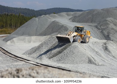 Orange wheel loader excavator in the background of a gravel storage in the open air. Mining industry. Quarry and mining equipment.