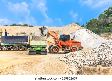 orange wheel loader loading gravel rock at gravel pit against blue sky.