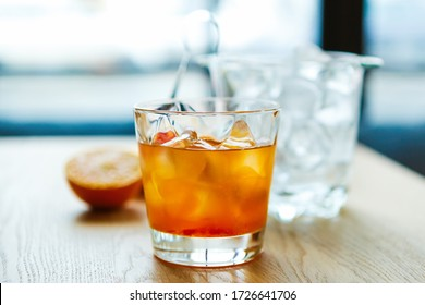 Orange whisky with ice in glass.Refreshing strong alocoholic long drink on table mixed by bartender in bar.Strong cocktail with bourbon whiskey,oranges slice.Tasty fresh alcoholic cocktails for party