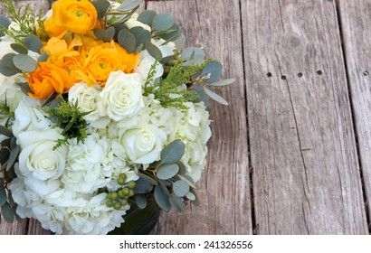 Orange and white bouquet of flowers on a farm table of distressed wood in farm country before a summer wedding, July 4, 2014
