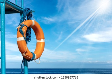 Orange and white life buoy with ropes hanging on a lifeguard chair with sea, blue sky, clouds and sun rays on background