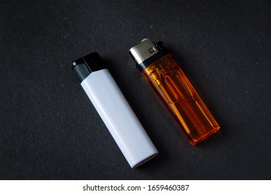 Orange, and white plastic gas lighter. Gas lighter on black background. Closeup shot, top view - Shutterstock ID 1659460387