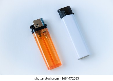 Orange, and white plastic gas lighter. Gas lighter on white background. Closeup shot, top view. - Shutterstock ID 1684472083