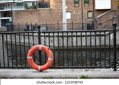 Orange and white ring flotation device by a river secured to black metal fence (railing) by a white rope. Device is used to help prevent people from drowning in the water