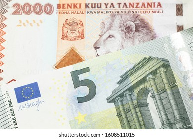 An orange and white two thousand Tanzanian shilling note with a blue and green euro note from the European Central Bank in macro