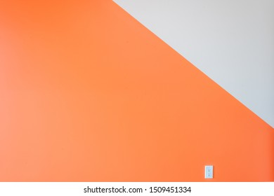 orange and white wall with electricity plug in a modern contemporary home