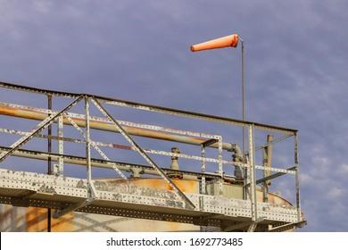 orange windsock on crude oil tanks