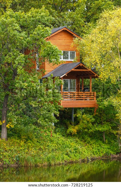 Orange Wooden Cottage On Piles Flying Stock Photo (Edit Now