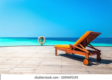 Orange wooden deck chair and lifebuoy on the wooden balcony of a luxury resort on the water against the backdrop of azure water, Maldives