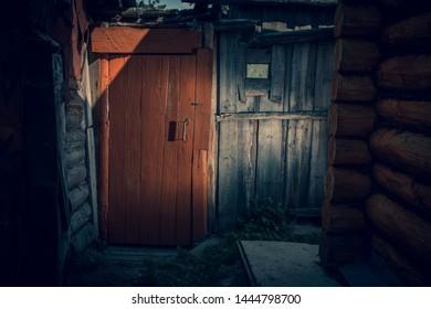 Orange wooden door in the hallway. Vintage, dark room.