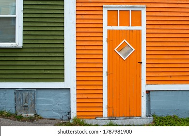 An orange wooden exterior door with a diamond shaped window in a building with orange and green wood clapboard. The trim on the building is white in colour. The concrete foundation is grey in colour.