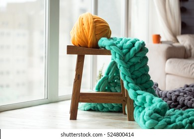 Orange wool ball with green knitted merino wool blanket on wooden chair, orange cup on a sofa at the background