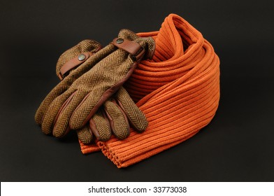 Orange wool scarf and brown leather and wool gloves on a black background