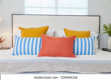 orange, yellow and blue pillows on white bed at home