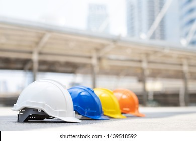 orange, yellow, blue and white hard safety wear helmet hat in the project at construction site building on concrete floor on city. helmet for workman as engineer or worker. concept safety first
