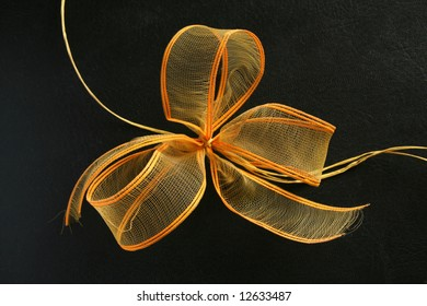 Orange and yellow ribbon bow on black background