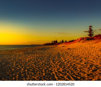 Orange and yellow sunset glows along the beach sand in Cottosloe Beach in Perth, Australia