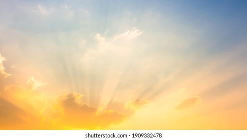 orange and yellow sunset light on sky with sun rays