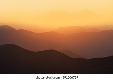 Orange and yellow sunset with mountains silhouettes. Gradient vivid  nature background.