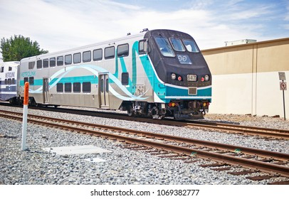 ORANGE/CALIFORNIA - APRIL 15, 2018: Metrolink train continues on its journey as it passes through the city of Orange after stopping at the station. Orange, California USA