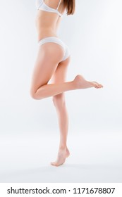 Orange-peel irritation concept. Vertical side profile view photo of long beautiful woman's legs standing on tiptoe wearing white underlinen lingerie isolated on background
