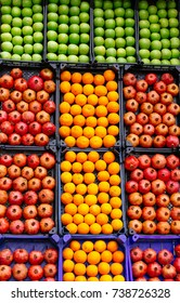 Oranges, apples, pomegranates in cases on the market selective focus