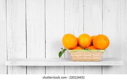 Oranges in a basket on a wooden shelf.