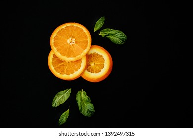 Oranges in a bowl / on paper with green leaves
