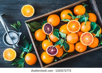 Oranges citrus fruits in wooden box on dark background and squeezer.