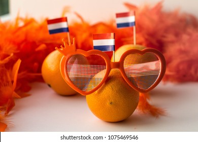 Oranges with Dutch flag and funny eye glasses on white background. Celebration of Dutch traditional king's day - Koningsdag. 27 april. Copy space