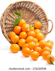 Oranges with leaves in a basket is scattered isolated on a on white