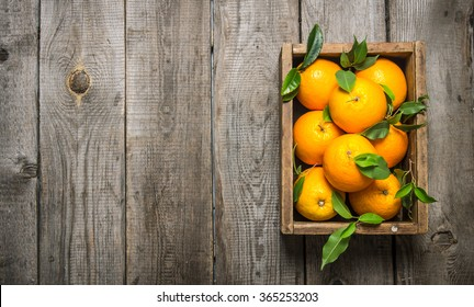 Oranges with leaves in an old box. On a wooden table. Free space for text . Top view
