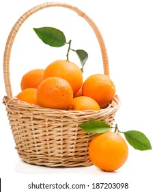 Oranges with leaves in wicker basket  with one on the surface in the foreground, isolated on white background.